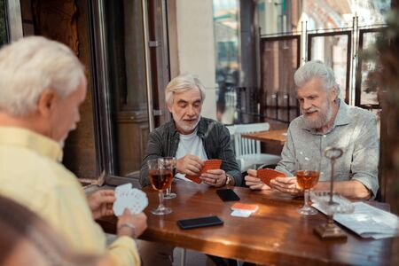 Cards and alcohol. Three retired aged men playing cards and drinking alcohol outside Imagens