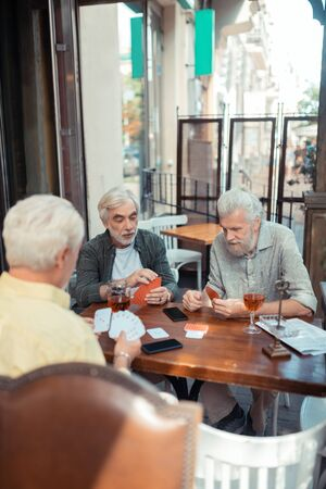 Sitting outside pub. Three aged retired men playing cars while sitting outside pub Imagens