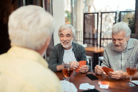Cards with friends. Aged bearded man laughing while playing cards with friends sitting outside pub Imagens