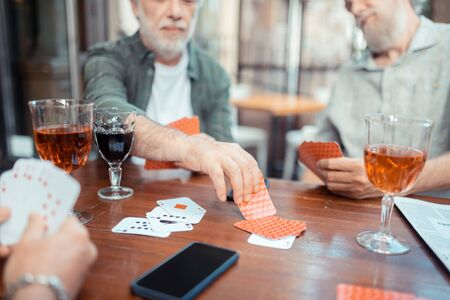 Cards and smartphone. Bearded grey-haired men drinking alcohol and playing cards sitting outside pub