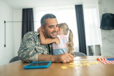 Officer feeling emotional. Handsome bearded military officer feeling emotional while hugging his cute lovely girl