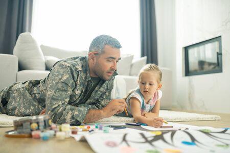 Dipingere con la figlia. Bell'uomo militare maturo che dipinge l'albero genealogico con sua figlia carina