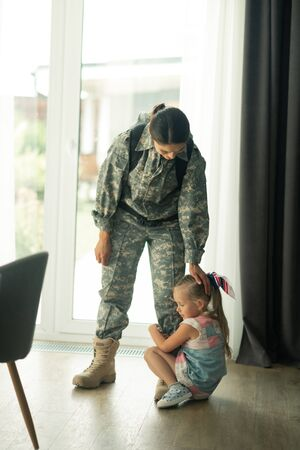 Lovely daughter. Dark-haired woman serving in armed forces touching her lovely daughter not letting her go