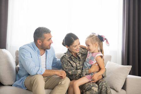 Wiedersehen zu Hause. Familie, die sich glücklich fühlt, während sie sich zu Hause mit einer nach Hause zurückkehrenden Militärfrau vereint Standard-Bild