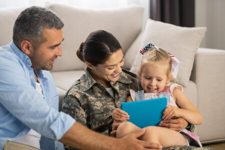 Unbelievably happy. Military woman feeling unbelievably happy watching cartoon with daughter and husband