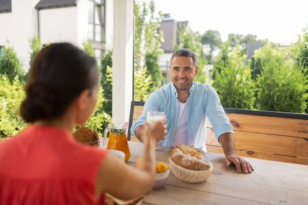 Breakfast with wife. Handsome bearded husband smiling while having breakfast outside with wife 免版税图像