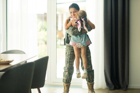 Mother back home. Woman wearing military uniform lifting her little daughter while coming back home