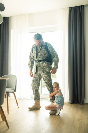 Saying goodbye. Man leaving home for military service saying goodbye to little emotional daughter