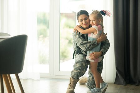 Blue-eyed daughter. Dark-haired military woman feeling happy while hugging cute blue-eyed daughter