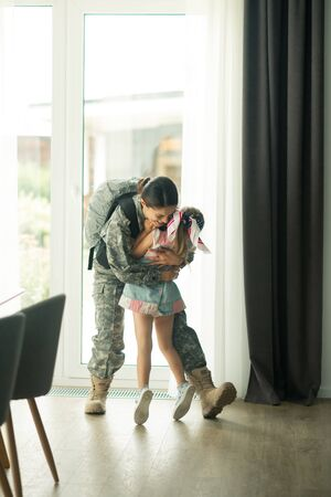 Hugging heroic mother. Daughter wearing dress hugging her heroic mother while returning home 免版税图像