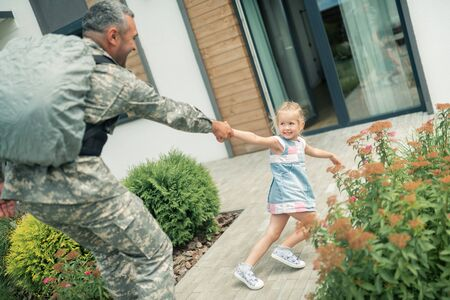 Father leaving. Blonde girl feeling unhappy while father serving as military man leaving for half a year Banco de Imagens