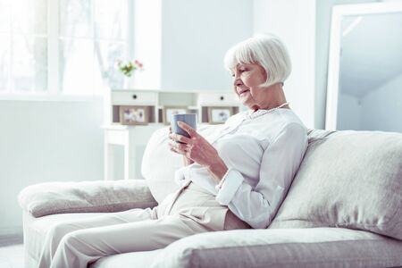 Elegant woman. Elegant retired woman feeling relaxed while drinking cup of tea sitting in cozy living room