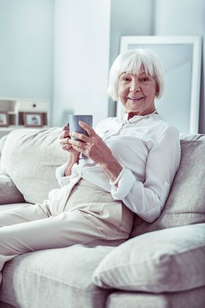 Day at home. Beaming retired woman feeling relieved while spending day at home drinking cup of tea