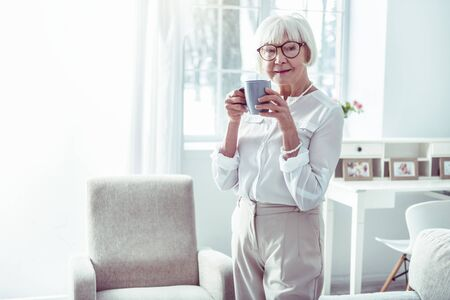 Business clothes. Elegant elderly lady wearing business clothes standing near window in living room