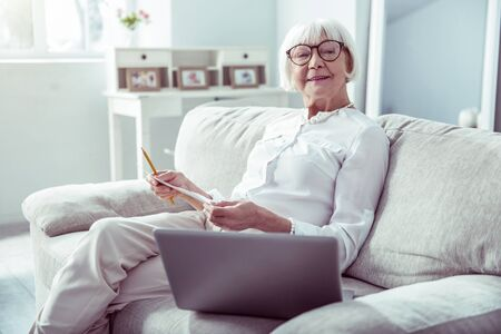 Woman in glasses. Retired woman wearing glasses watching video on her laptop and making notes