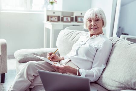 Relaxed woman. Stylish elegant elderly lady feeling truly relieved and relaxed having rest in living room Фото со стока