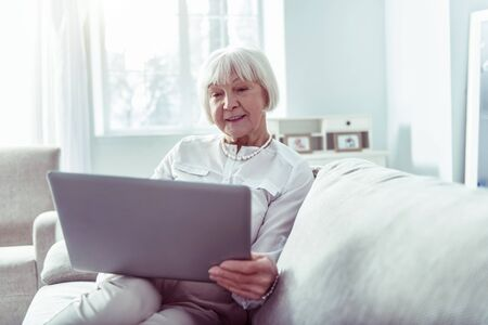 Video chat. Beaming dark-eyed elderly lady feeling happy having video chat with daughter using laptop