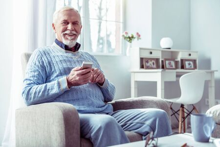Day at home. Cheerful bearded retired man feeling extremely relaxed and happy spending day at home