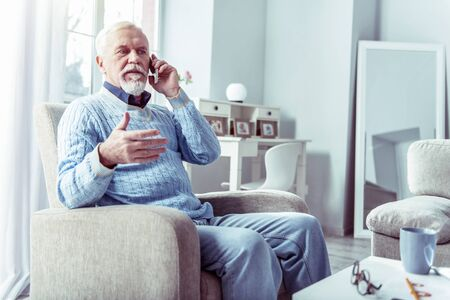 Elderly businessman. Elderly working businessman feeling a little bit busy calling his partners from home