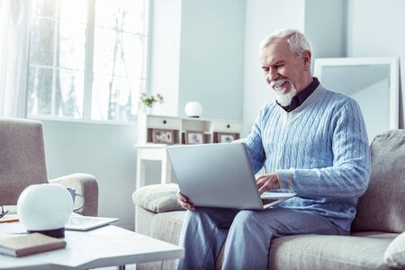 Video chat. Smiling bearded retired man wearing blue sweater looking at laptop while having video chat