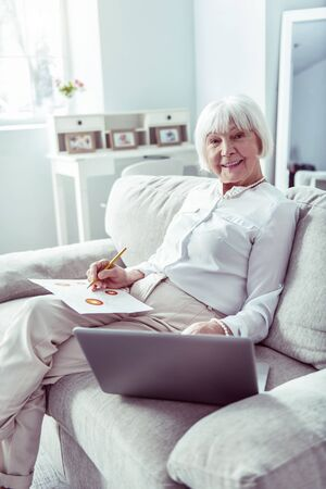 Lady with pencil. Creative elderly lady holding pencil while drawing sitting on sofa in living room Фото со стока