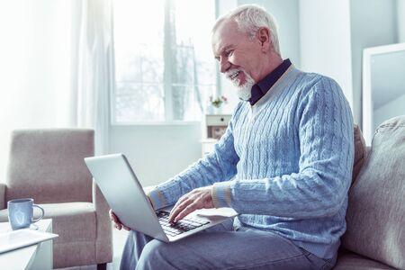 Man on sofa. Beaming bearded retired man sitting on grey sofa having video chat using his laptop Фото со стока