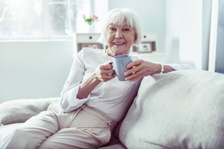 Smiling lady. Smiling elderly lady wearing nice stylish white blouse sitting in living room drinking cup of tea Фото со стока