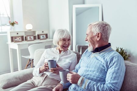 Couple of pensioners. Beaming couple of pensioners feeling extremely lovely and happy enjoying tea time together Фото со стока
