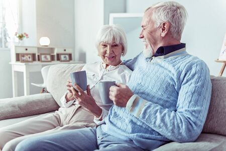 Caring man. Caring loving retired man hugging his cute elegant wife sitting on sofa and drinking some tea