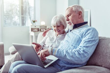 Modern grandparents. Couple of modern cheerful happy grandparents looking at laptop while having video chat Фото со стока