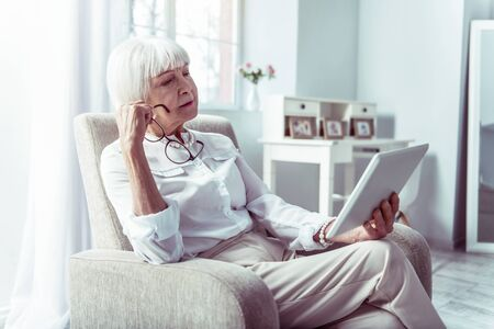 Reading news. Blonde-haired elderly lady feeling thoughtful while reading local news on tablet in living room Фото со стока