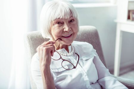 Smiling broadly. Close up of beautiful elderly lady with facial wrinkles smiling broadly after family dinner Фото со стока