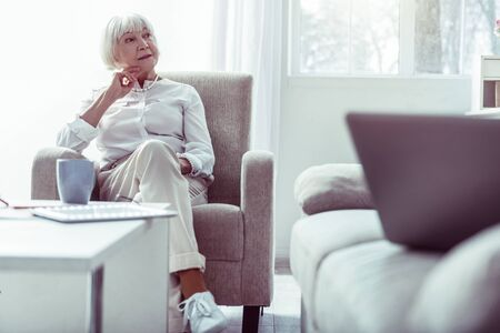 Pleasant grandmother. Stylish pleasant grandmother wearing white sneakers sitting in living room drinking tea