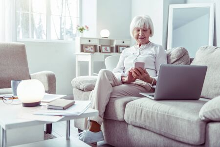 Smartphone and laptop. Modern elderly businesswoman sitting in living room with smartphone and laptop
