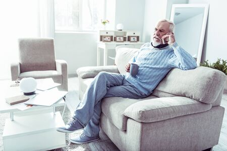 Calling wife. Stylish retired man holding his phone while calling wife from home while drinking some tea Фото со стока