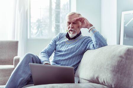 Modern man. Modern retired man wearing white smart watch looking at his laptop sitting on grey sofa Фото со стока