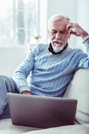 Stylish man. Stylish bearded retired man wearing blue sweater using his silver laptop sitting in living room
