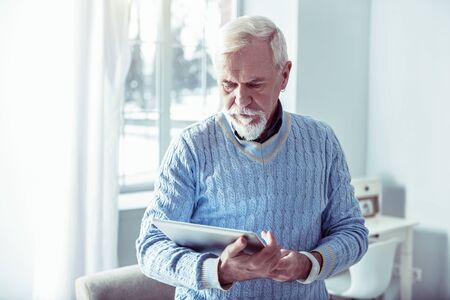Silver laptop. Bearded grey-haired man feeling good while holding silver laptop watching photos Фото со стока