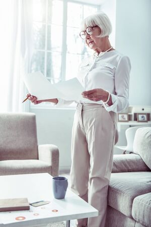 Family business. Slim beautiful retired woman wearing beige trousers and white blouse doing family business
