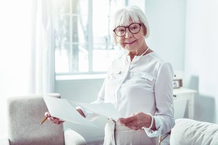 Happy woman. Elegant fashionable retired woman wearing glasses feeling extremely happy and cheerful Фото со стока