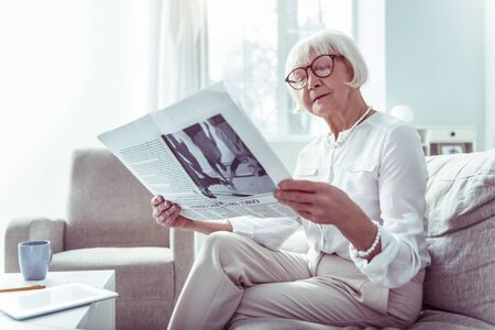 Morning newspaper. Beautiful elderly lady wearing glasses and white blouse reading morning newspaper sitting on sofa