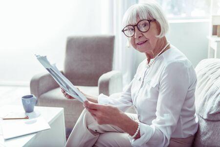 Local news. Pleasant stylish elegant elderly lady feeling joyful while reading local news at home