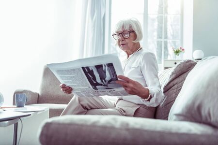 Waiting for husband. Beautiful elderly woman reading newspaper while waiting for husband at home in light room