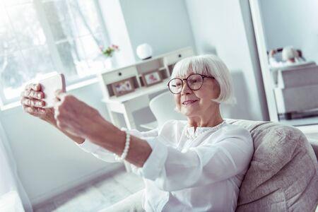 Making selfie. Modern beaming smiling elderly lady holding her smartphone and making selfie