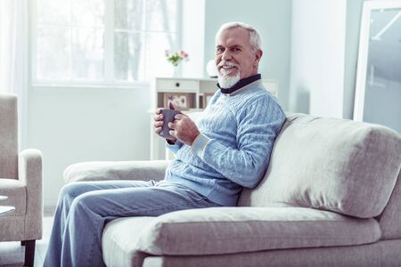 Man in jeans. Beaming retired man wearing jeans and blue sweater drinking some tea sitting on grey sofa Фото со стока