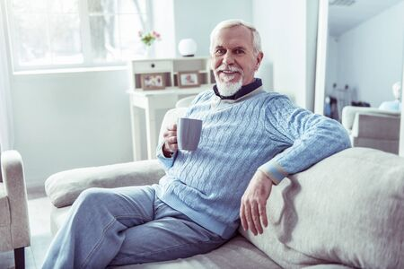Rest at home. Modern retired man feeling relieved having some rest at home drinking cup of tea Фото со стока