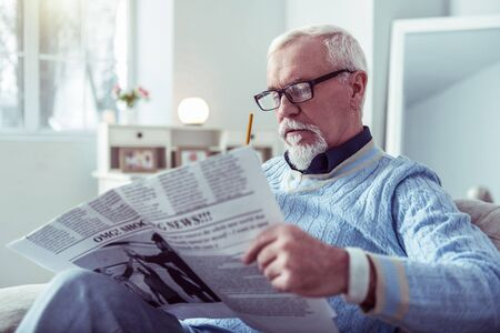 Man with earring. Bearded grey-haired retired man with earring in his ear watching morning newspaper
