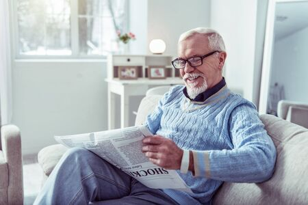 Positive news. Grey-haired retired man wearing blue sweater smiling while reading positive local news