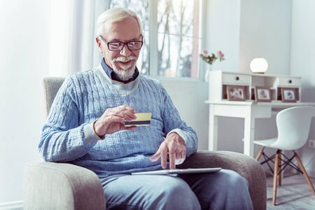 Shopping online. Grey-haired retired modern man holding bank card while shopping online from home