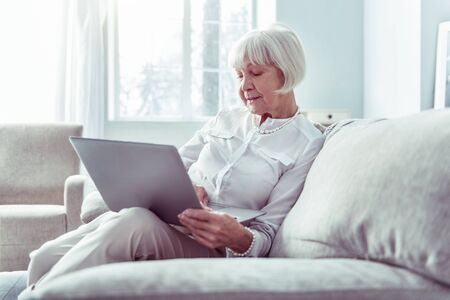 Modern woman. Modern retired woman holding silver laptop while watching video with her grandparents Фото со стока